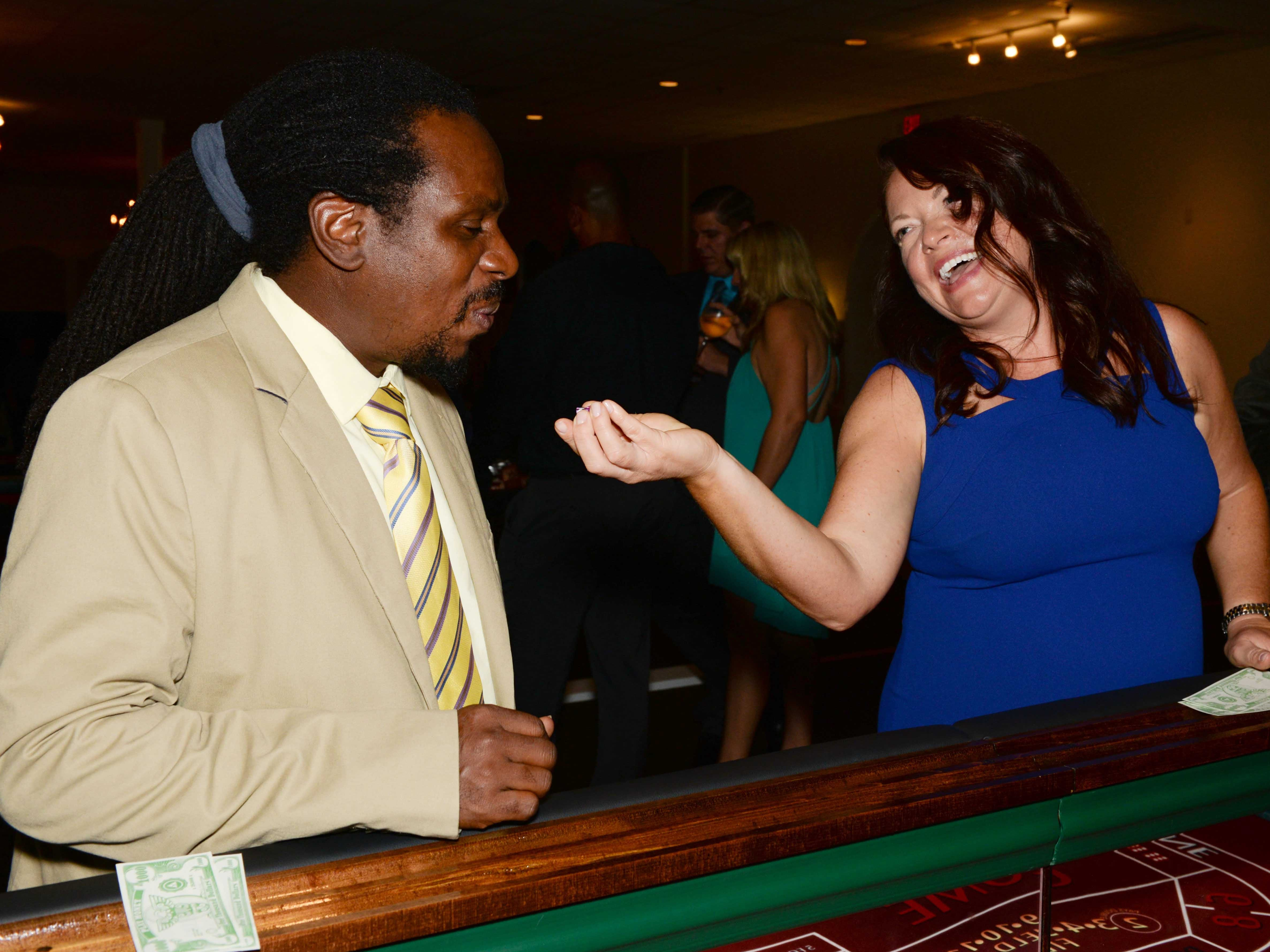 "Molly Gereaud, right, has Duane Turner blow on the dice for luck at Renaissance Charter School of St. Lucie's ""Viva Las Vegas"" gala and benefit auction."