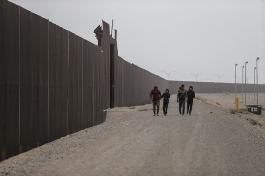 Four young migrants walk on a dirt road along the border fence in El Paso.