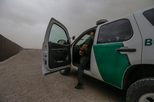 A U.S. Border Patrol agent waits as migrants approach his truck along the border fence in El Paso, Texas.