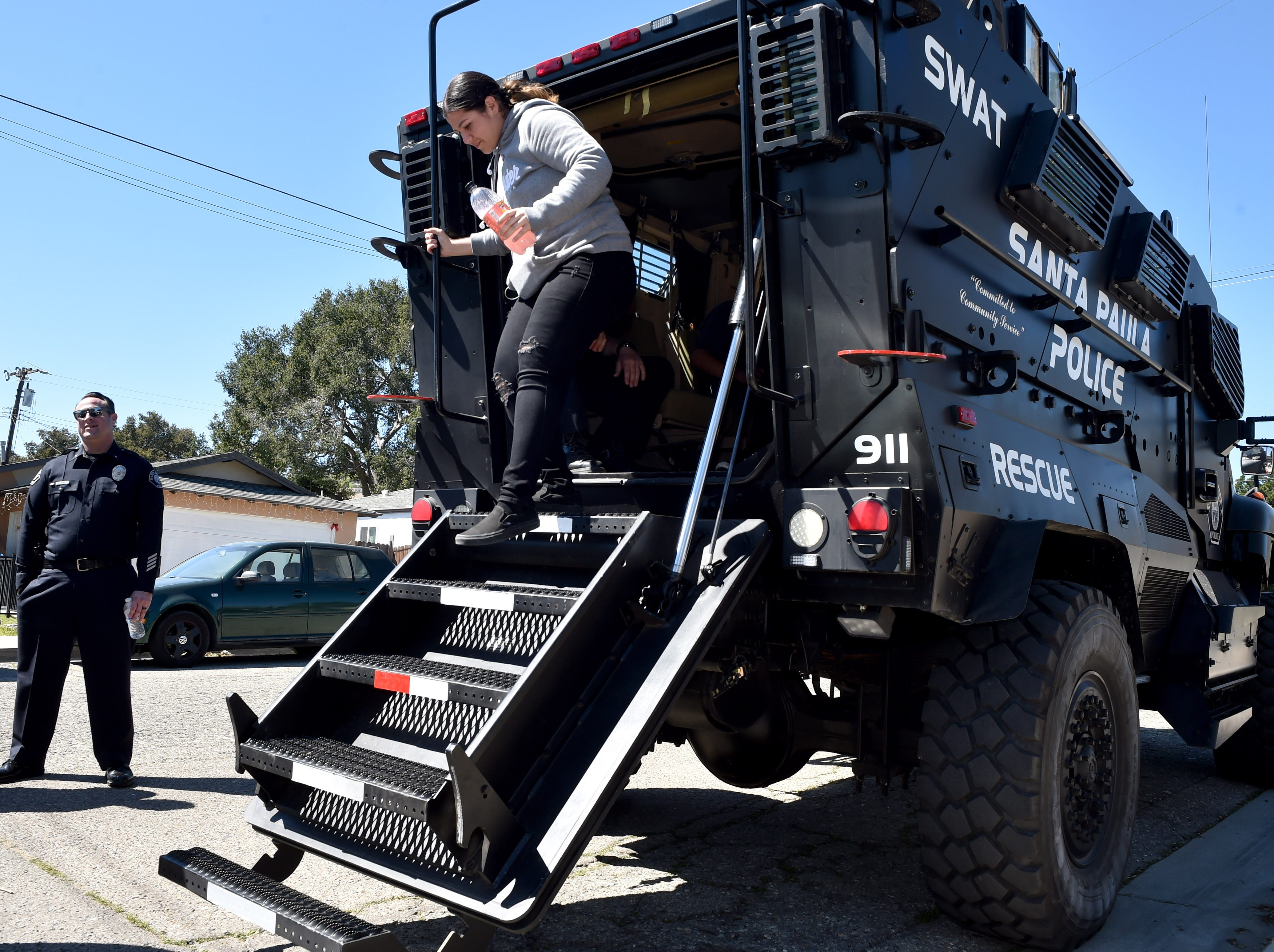 Navaeh Delgadillo, 16, climbs down after exploring a SWAT vehicle at the Santa Paula Police Department's youth center on Friday.