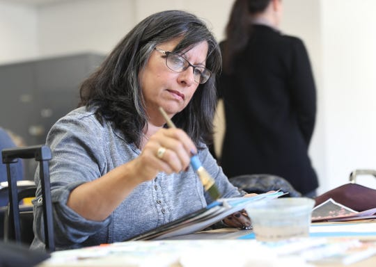 Kim Tortolani of White Plains works brush strokes on a project at the Westchester Community College's Center for the Arts program at the County Center in White Plains on Monday, March 18, 2019.