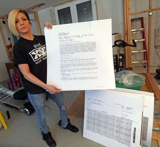 Catherine Marino, a Bardonia mother who underwent multiple surgeries shows documents at her home March 18, 2019, from malpractice lawsuit that were found on the floor of a flooded county bathroom.