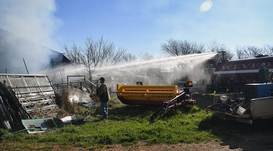 A tanker-mounted turret blasts water into a hay barn as a man uses a garden hose to help fight a blaze that consumed about 800 bales of hay Monday morning.