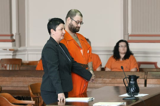 Attorney Nicole Churchill holds the hand of her client, Matthew Stickdorn, as Stickdorn is sentenced in Muskingum County Common Pleas Court on Monday.