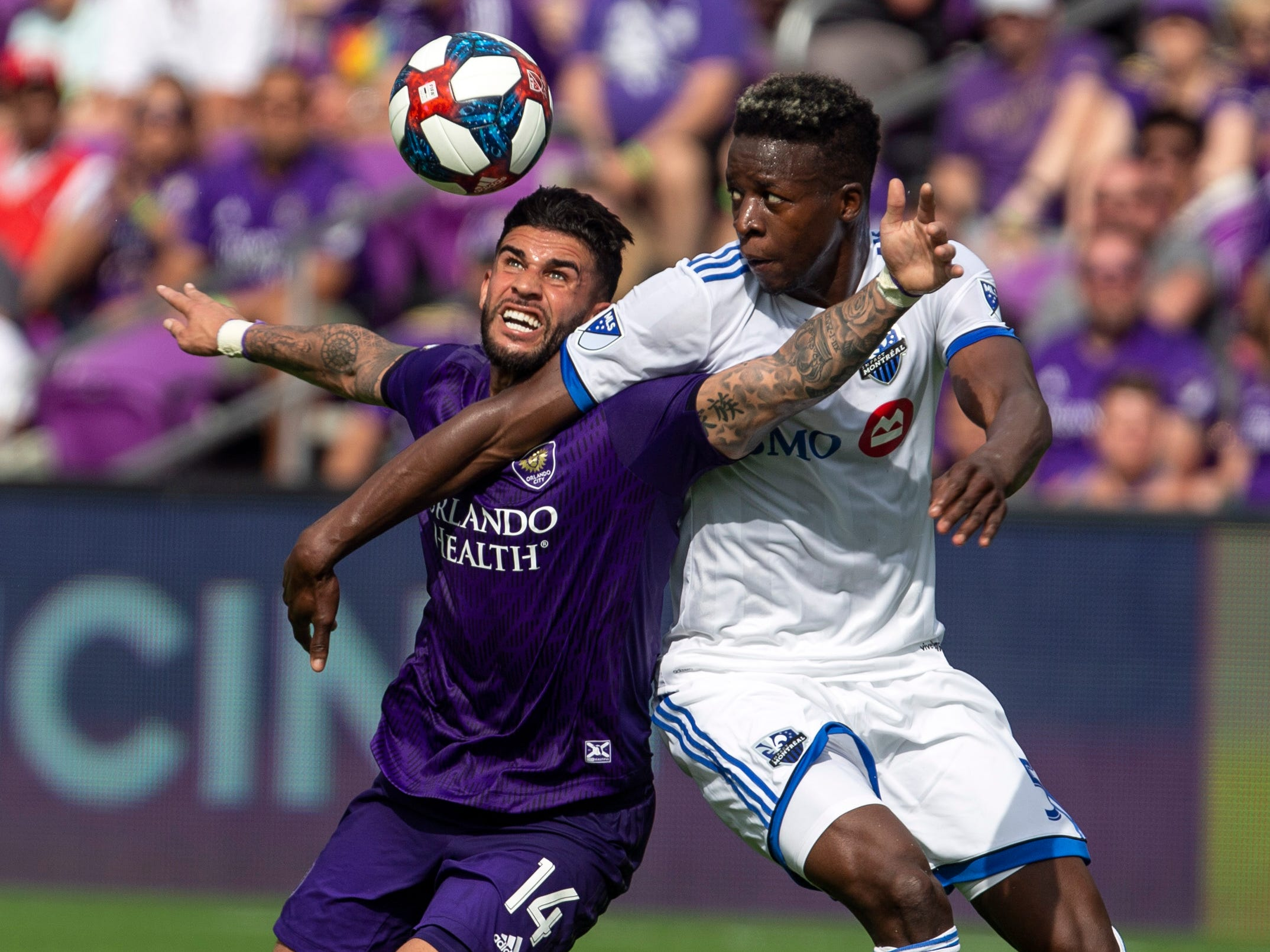 March 16: Orlando City forward Dom Dwyer (14) and Montreal Impact defender Zakaria Diallo (5) fight for the ball during the first half at Orlando City Stadium. Montreal won the game, 3-1.