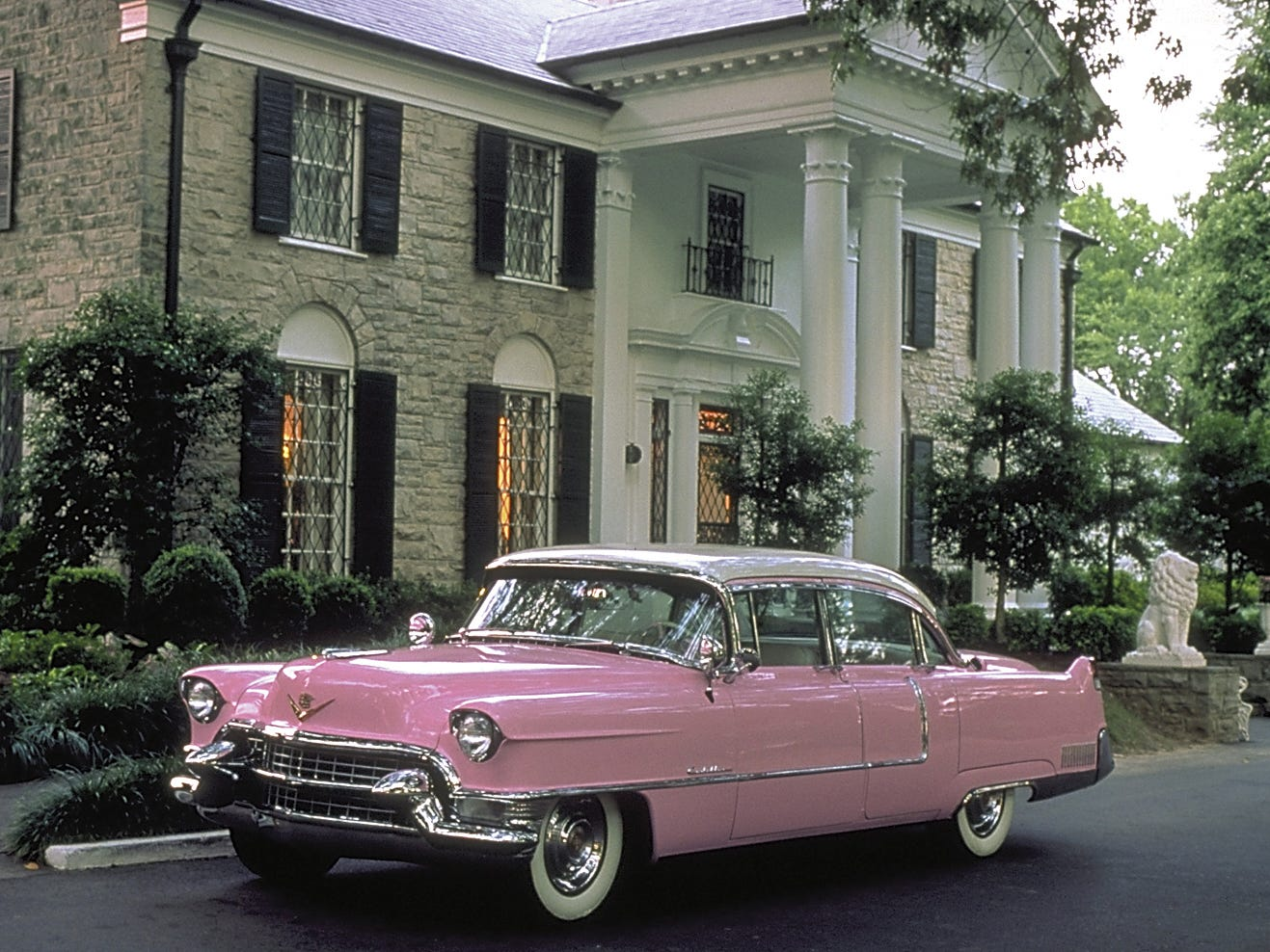 A vintage pink Cadillac parked in front of Graceland.