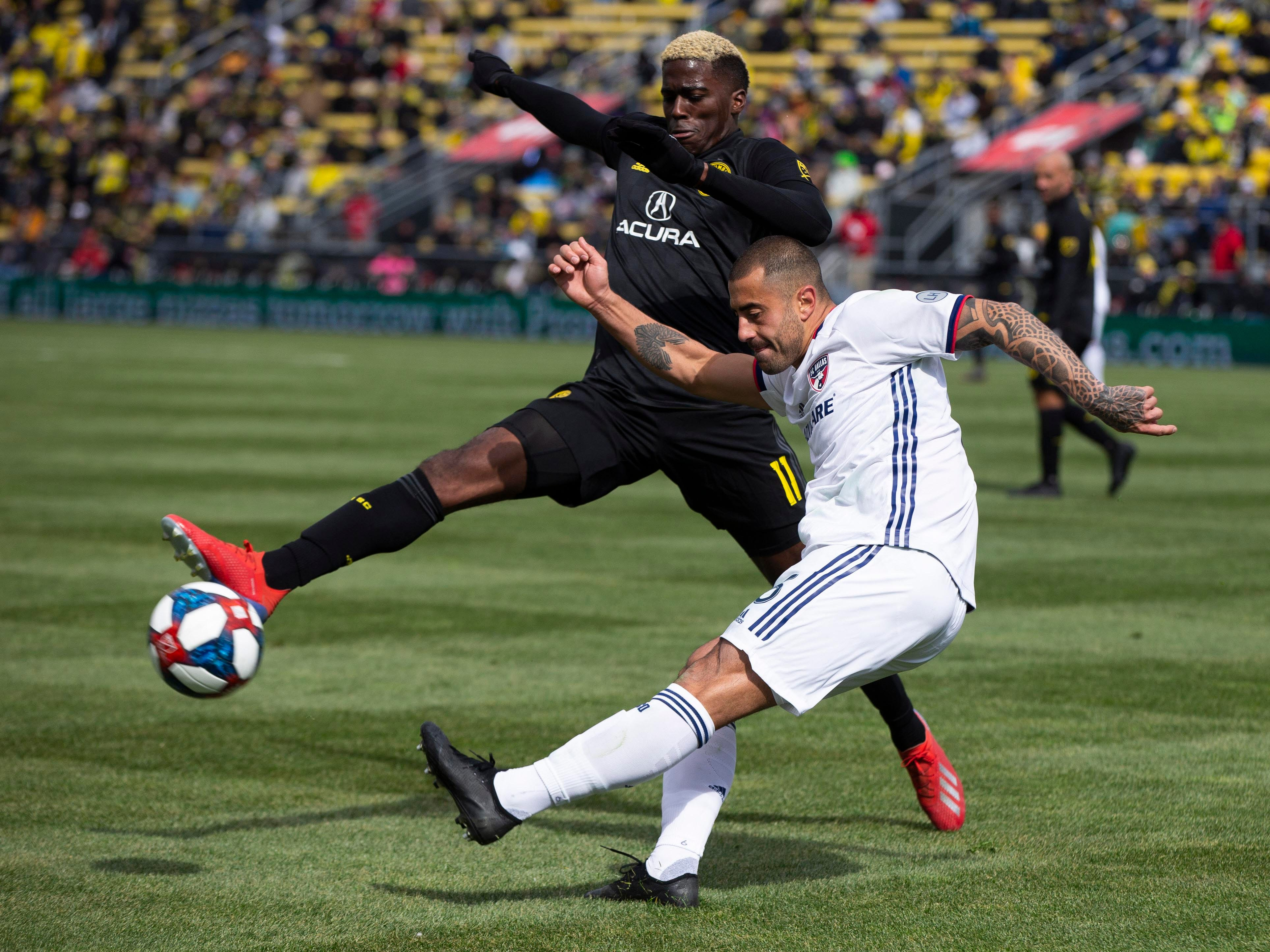 March 16: Columbus Crew SC forward Gyasi Zardes (11) tries to block a clearance from FC Dallas defender Marquinhos Pedroso at MAPFRE Stadium. Columbus won the game, 1-0.