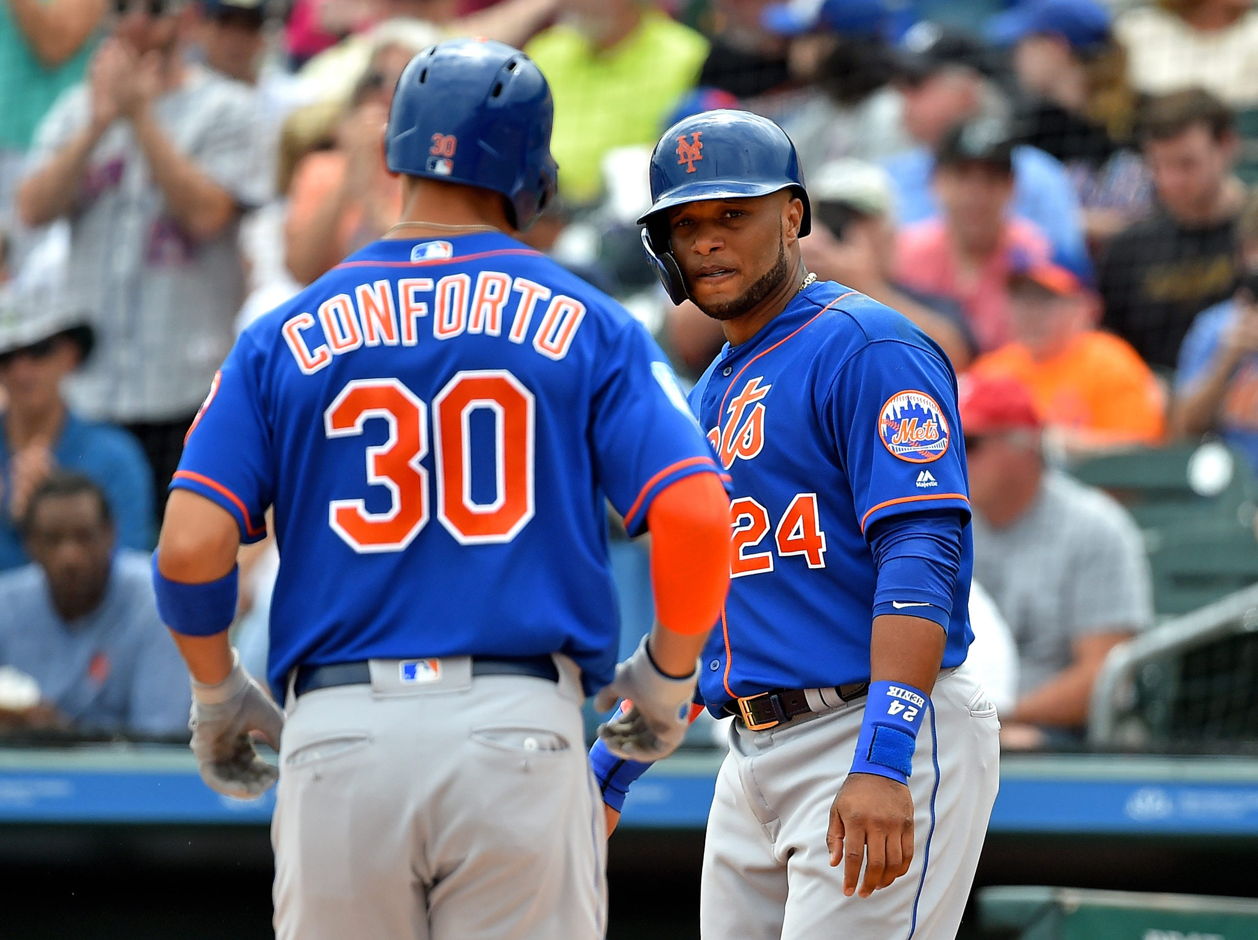 March 16: Robinson Cano celebrates with Michael Conforto after a two-run homer against the Marlins.