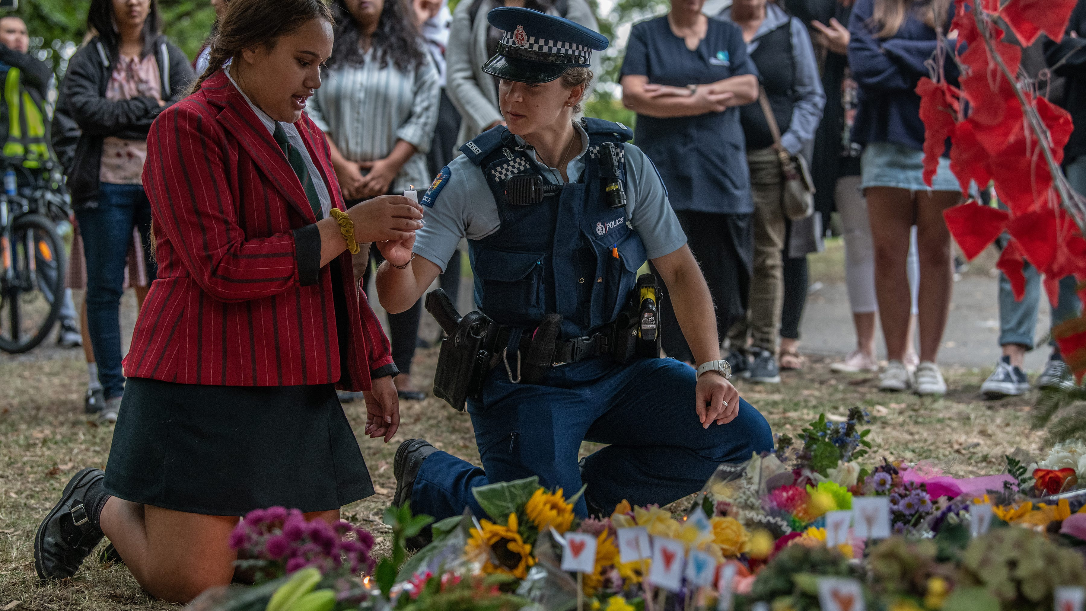 A police officer passes a candle to a schoolgirl during a students vigil near Al Noor mosque on March 18, 2019 in Christchurch, New Zealand.