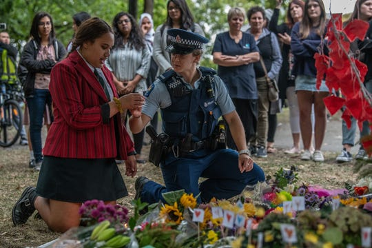 A police officer passes a candle to a schoolgirl during a students vigil near Al Noor mosque on March 18, 2019, in Christchurch, New Zealand.