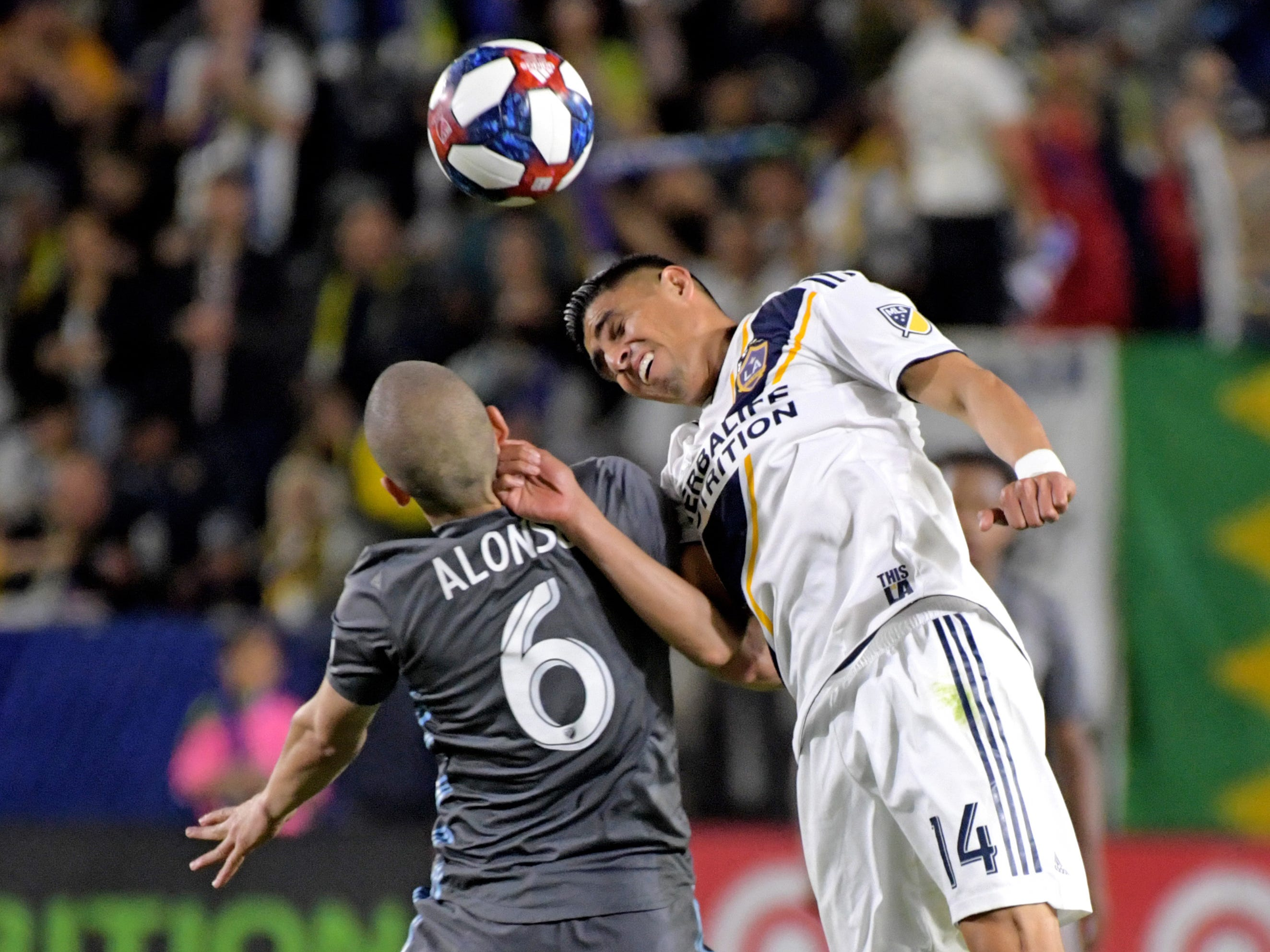 March 16: LA Galaxy midfielder Joe Corona (14) heads the ball against Minnesota United midfielder Osvaldo Alonso (6) in the second half at Dignity Health Sports Park. The Galaxy won the game, 3-2.