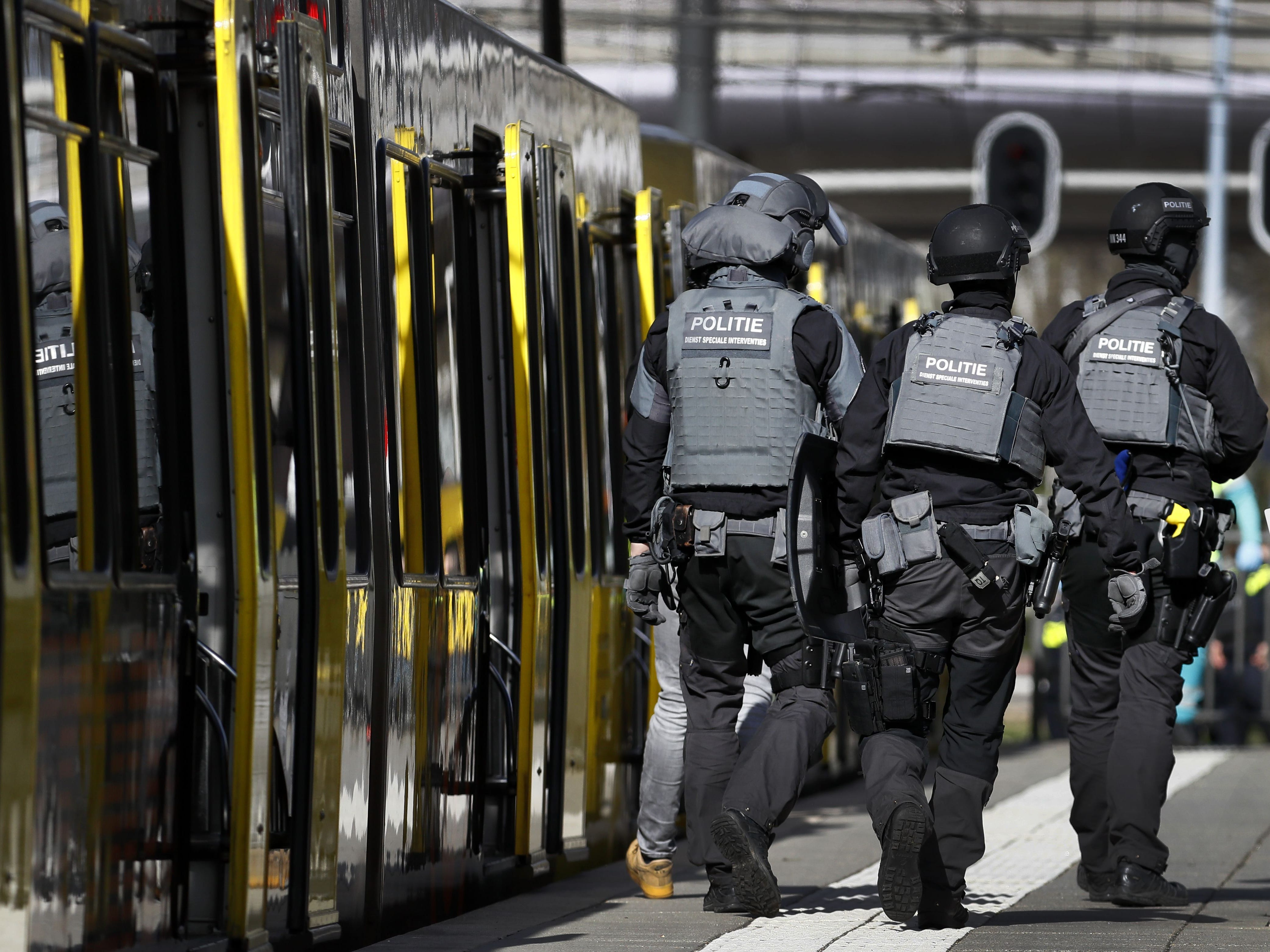 Police forces walk near a tram at the 24 Oktoberplace in Utrecht, on March 18, 2019 where a shooting took place.