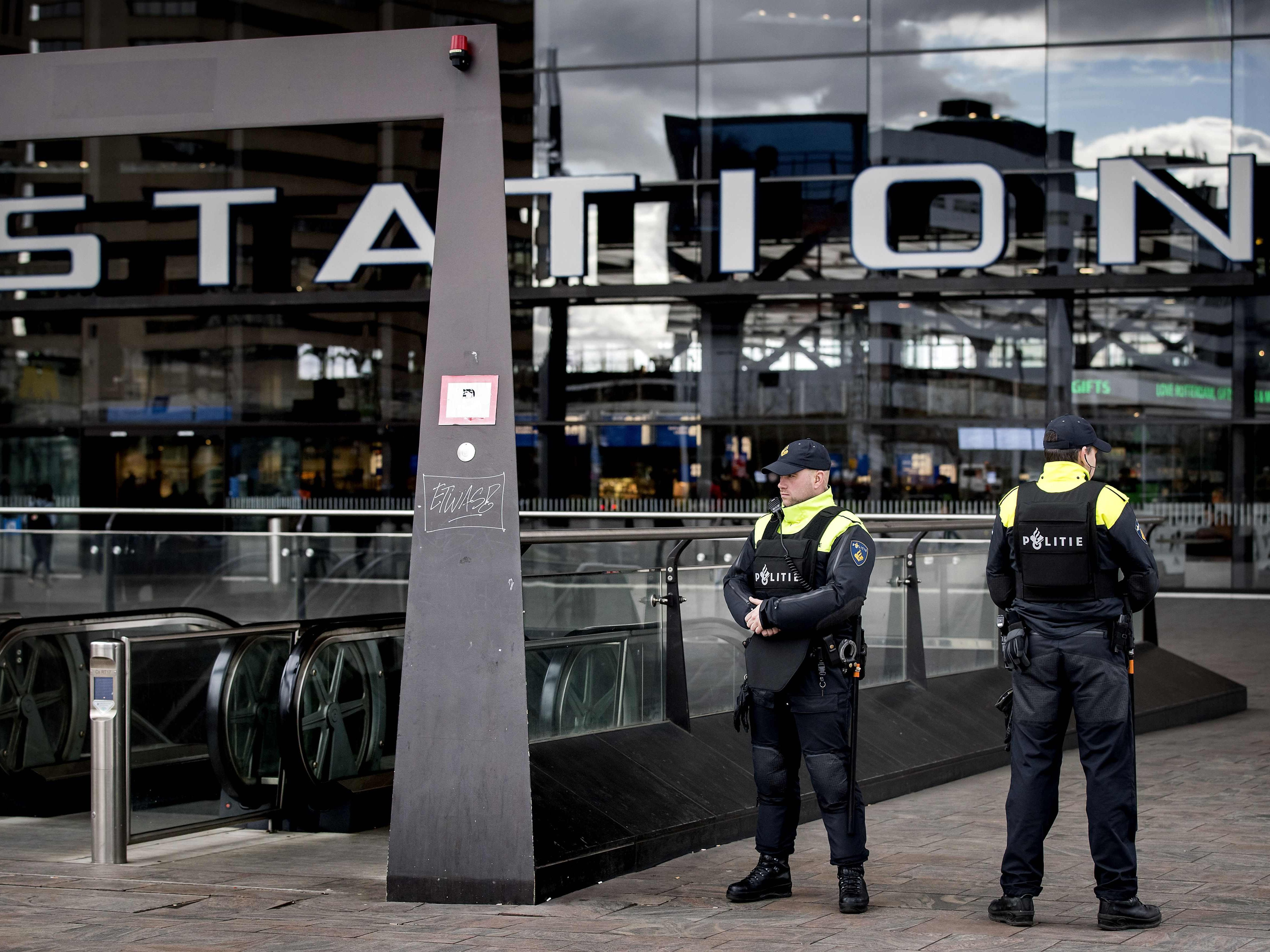 Officers keep surveillance at the entrance of a station in Rotterdam, after the attack in Utrecht.