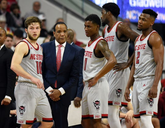 North Carolina State Wolfpack head coach Kevin Keatts (second from left) talks to his players during a timeout.