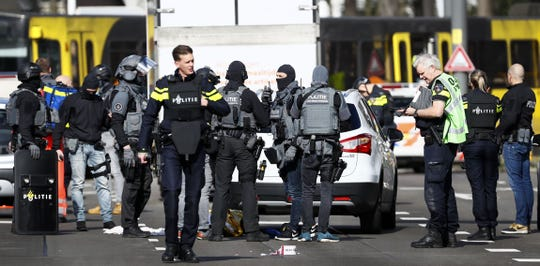 Police forces stand near a tram at the 24 Oktoberplace in Utrecht, on March 18, 2019 where a shooting took place.  A gunman who opened fire on a tram in the Dutch city of Utrecht on March 18, injuring several people, is on the run, police said.
