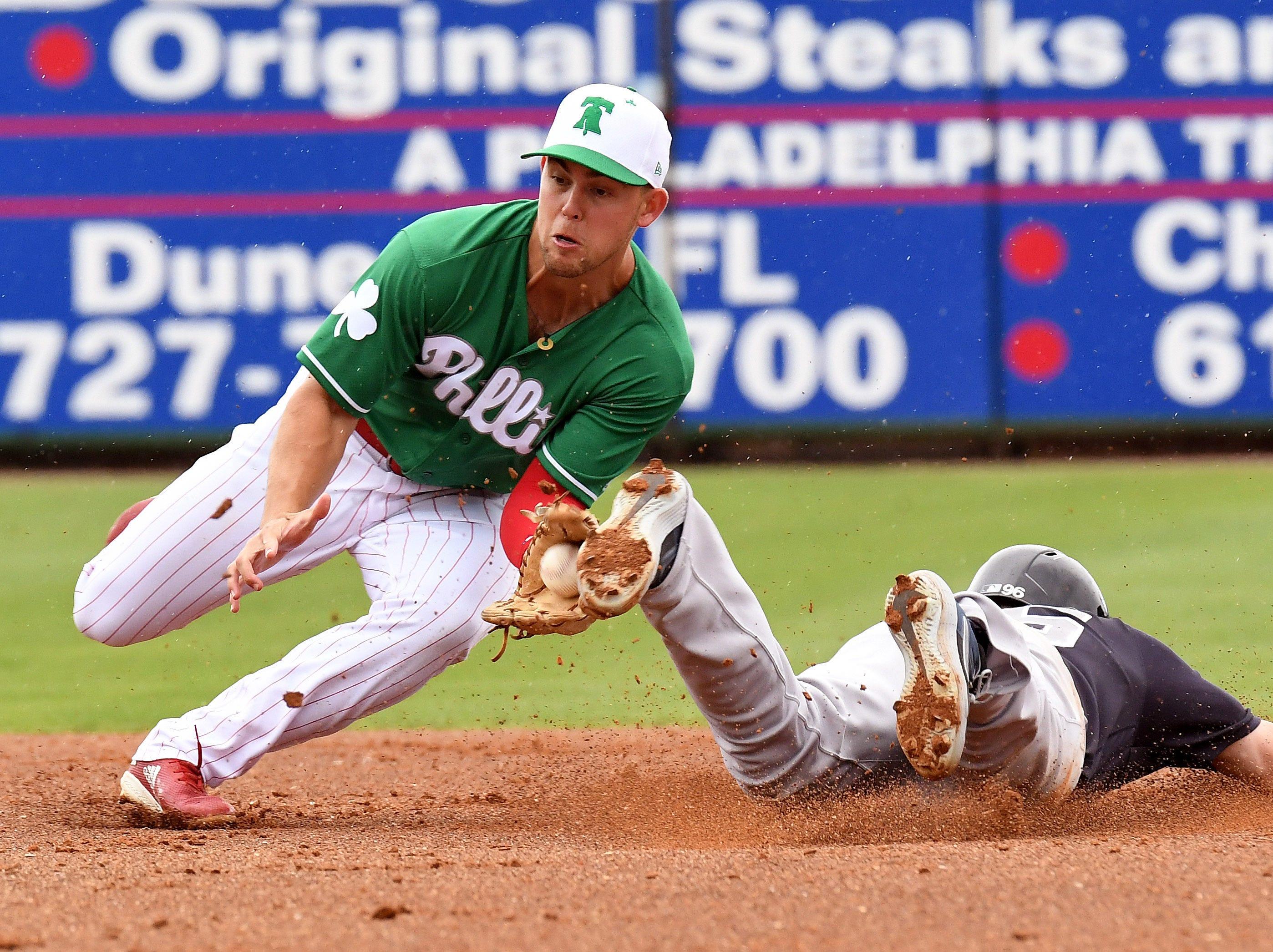 March 17: Phillies infielder Scott Kingery fields a throw as Yankees outfielder Matt Lipka slides into second.