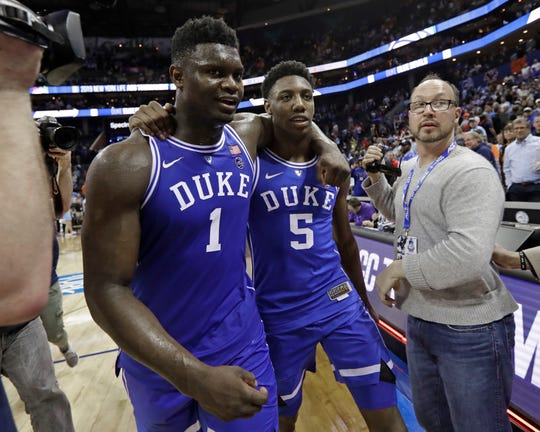 Duke's Zion Williamson (1) and R.J. Barrett (5) embrace as they leave the court after Duke defeated North Carolina in an NCAA college basketball game in the Atlantic Coast Conference tournament.