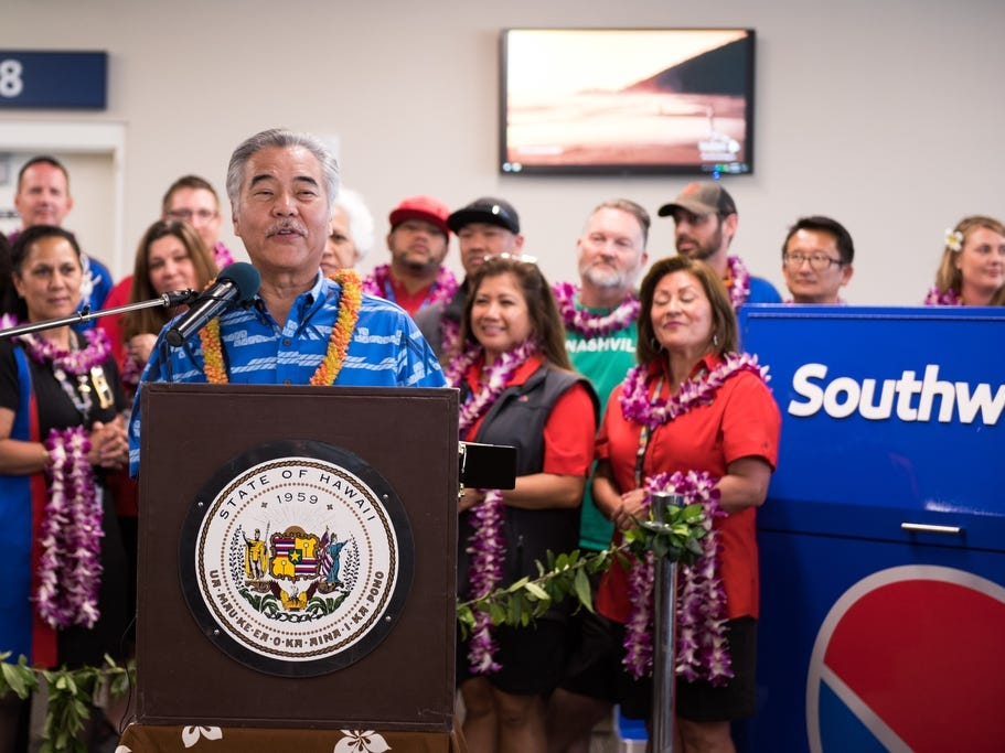 Hawaii Governor David Ige greets passengers on Southwest Airlines' inaugural Hawaii flight at the Daniel K. Inouye International Airport in Honolulu.