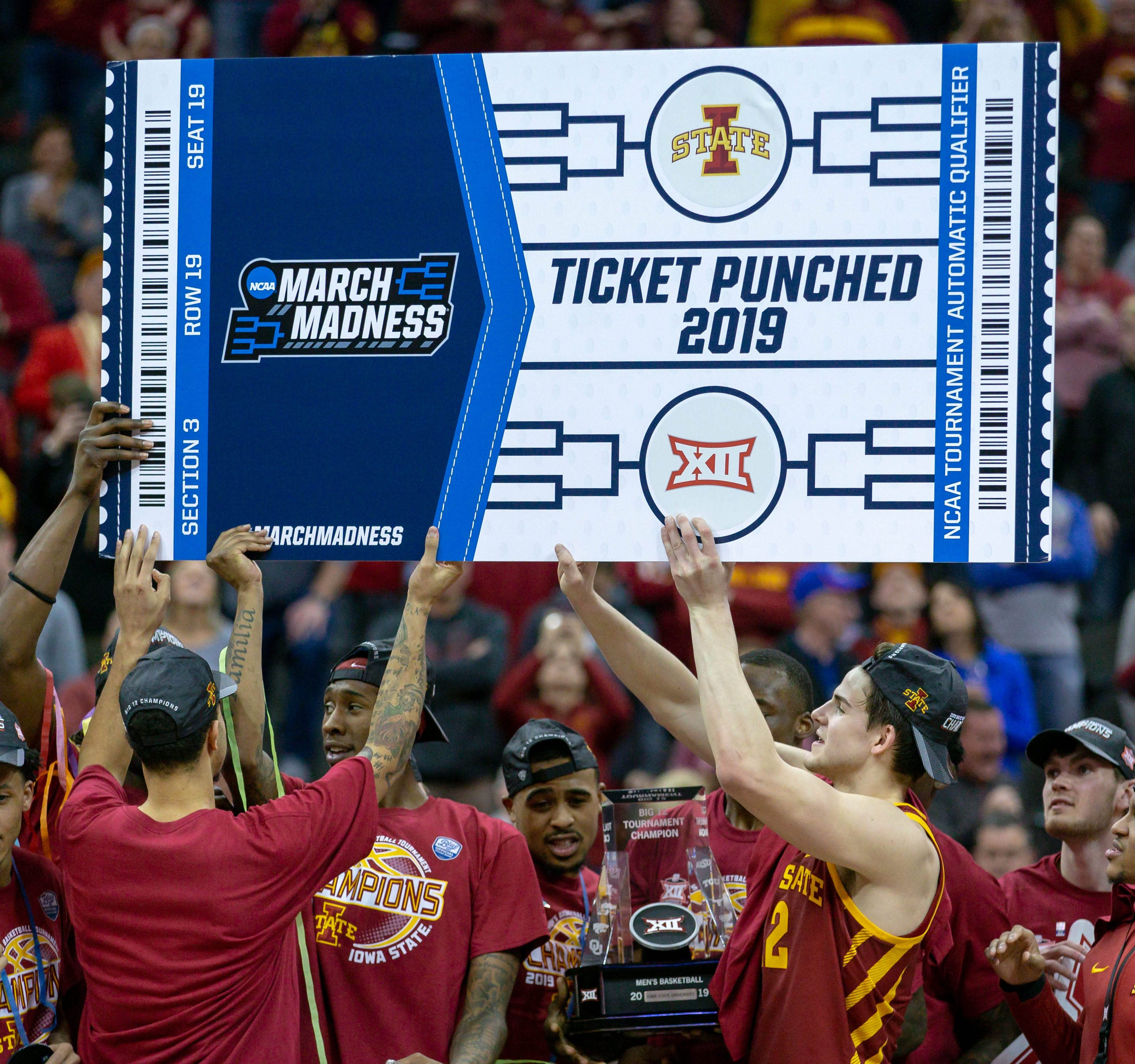 Iowa State players hold up a March Madness tournament ticket after the Big 12 championship game.