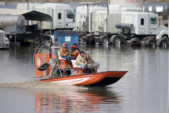 Gabe Schmidt, owner of Liquid Trucking, top right, travels by air boat with Glenn Wyles, top left, Mitch Snyder, bottom left, and Juan Jacobo, bottom right, as they survey damage from the floodwaters of the Platte River in Plattsmouth, Neb., on March 17, 2019.