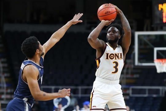 Iona Gaels guard Asante Gist (3) shoots the ball against the defense of Monmouth Hawks guard Nick Rutherford (5) during the second half in the MAAC Conference Tournament