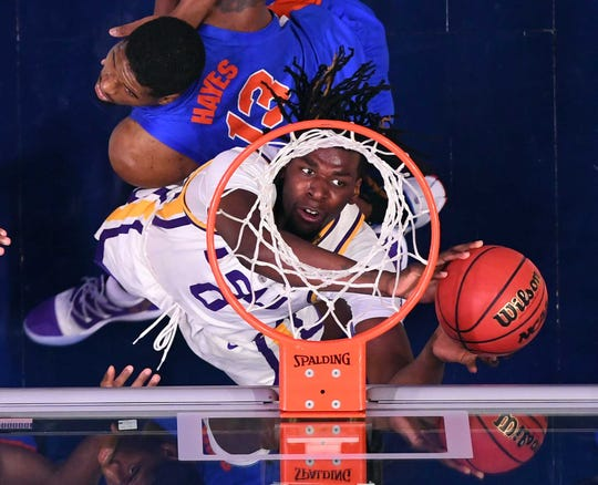 LSU Tigers forward Naz Reid (0) puts in a rebound behind pressure from Florida Gators center Kevarrius Hayes (13) in the SEC conference tournament