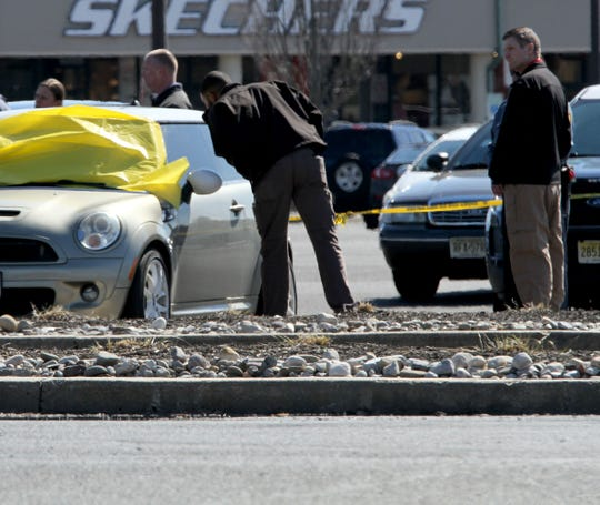 Jackson Township police officers are shown around a car where person was discovered shot in the parking lot at the Jackson Factory Outlets Tuesday morning, March 19, 2019.