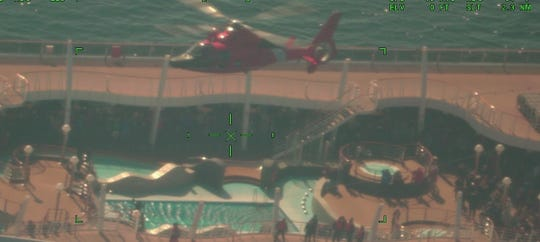 An MH-65 Dolphin helicopter crew from Air Station Atlantic City airlifts a sick passenger from the ocean liner MSC Divina, in this photo taken from an HC-130 Hercules airplane crew from Air Station Elizabeth City, North Carolina.
