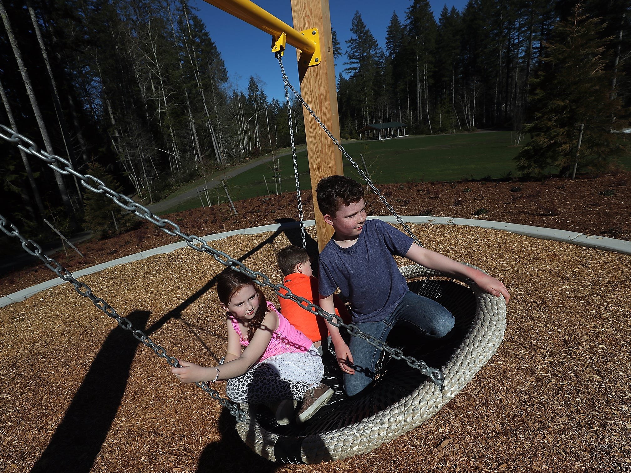 Avery Edwards , 9, and her siblings Luke, 5, and Zack, 11, ride the swing at McCormick Woods Park in Port Orchard on Monday March 18, 2019. The siblings had spent the last three days playing in the new park and Zack was hoping that they could make it back the next day as well.
