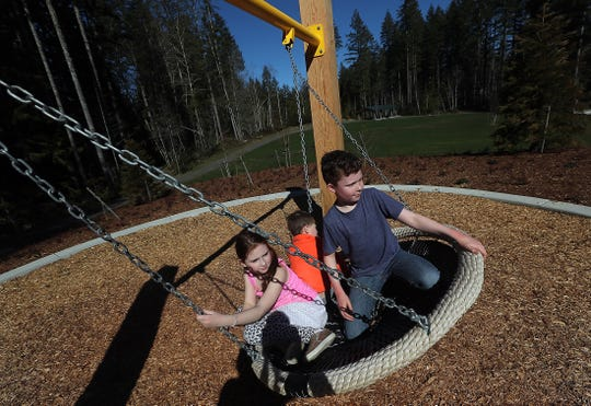 Avery Edwards, 9, and her siblings Luke, 5, and Zack, 11, ride the swing at McCormick Woods Village Park in Port Orchard on Monday. The siblings had spent the last three days playing in the new park and Zack was hoping that they could make it back the next day as well.