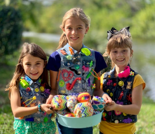 Clara Drew Day, Elena Day and Scarlett Uhle show off the wrapped surprises they'll be selling at the Brevard Children's Business Fair on March 30. You won't know what's inside until you open your purchase, making it even more fun, the girls say.