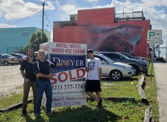 "Steve Young (pointing) poses alongside sons Austin (left) and Chase (right) by the ""Sold"" sign at Eau Gallie's ""sharking lot."""