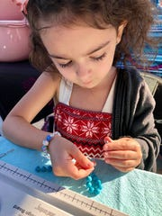 Ella Grace Helton, 6, works on some of her Ella Bella Beads creations, which she'll be selling at the March 30 Brevard Children's Business Fair.