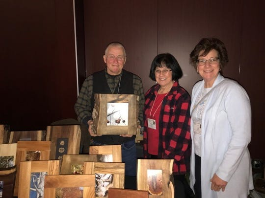 During the March 5 Wildlife Diversity Conference,on the campus of The Ohio State University, Randy Sanders shared his wood frames rendered from trees with Mary Lee Minor and June Gebhardt.