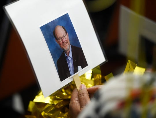 Press conference attendees holds a sign with Robert Thompson's face on it during the teacher of the year press conference, Tuesday, March 19, 2019, at the CCISD Administration Building. Many attendees held pom-poms throughout the ceremony.