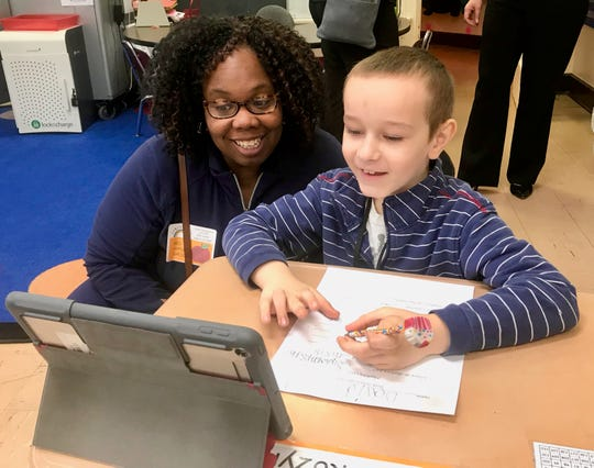 David Kozyra, a first-grader at School No. 8 in Linden, discussing a story he was reading on his iPad with a visitor to his classroom on March 12. The tour was part of School No. 8's inclusion in the Apple Distinguished Schools program.