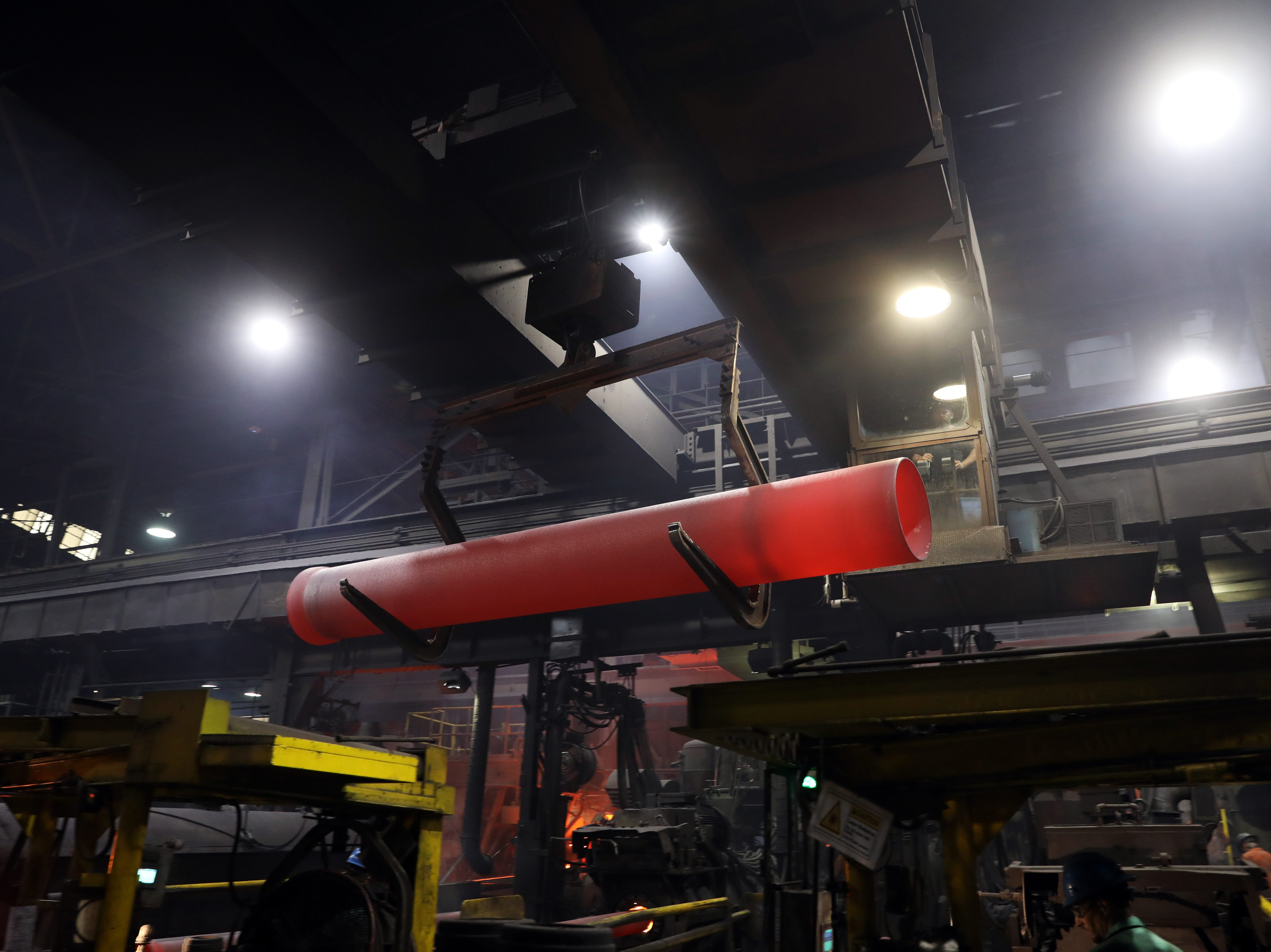 A red-hot pipe fresh from a machine is carried on a crane at McWane Ductile in Coshocton.