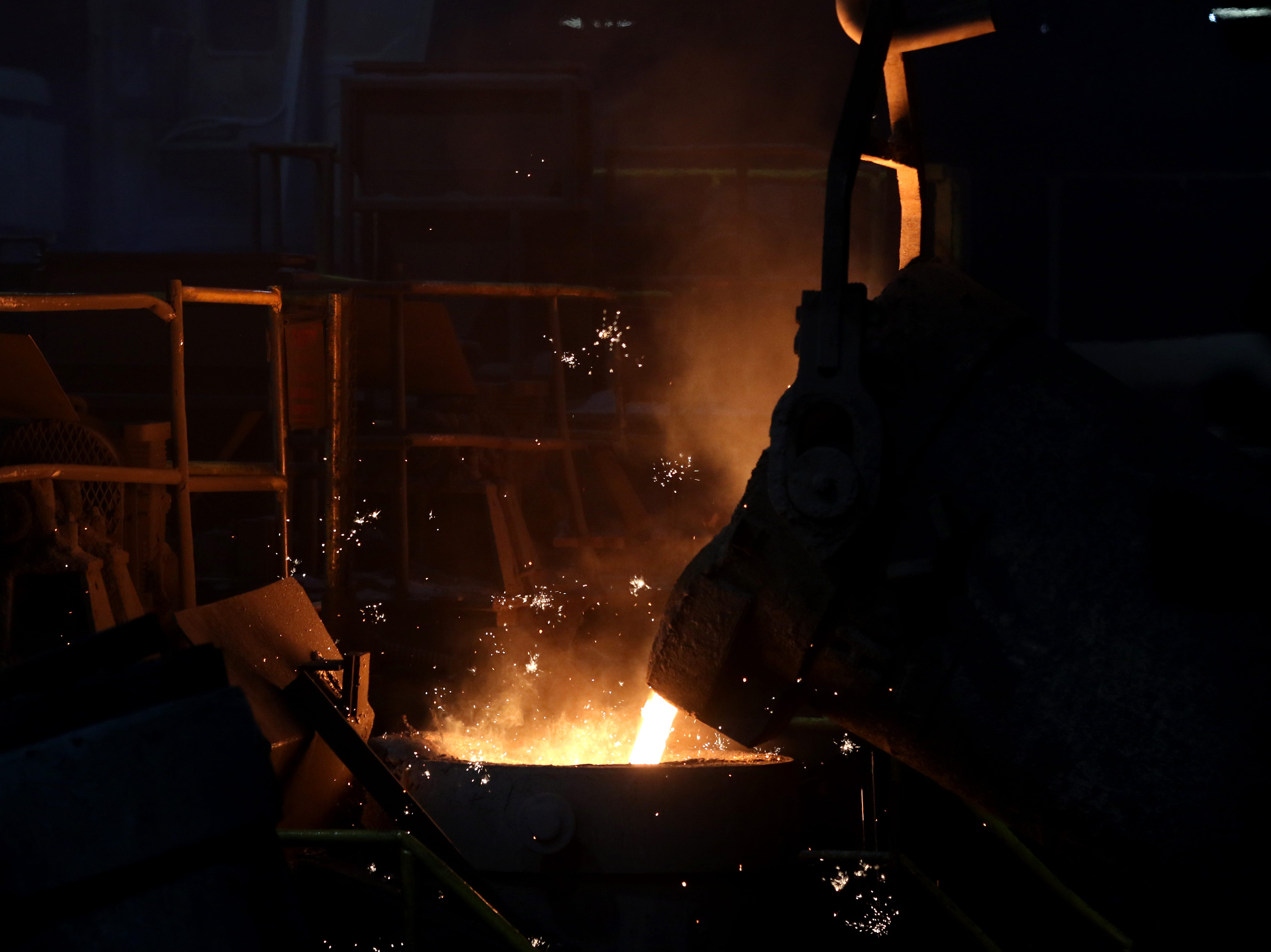A crane pours a crucible of molten iron into a pipe making machine at McWane Ductile in Coshocton.