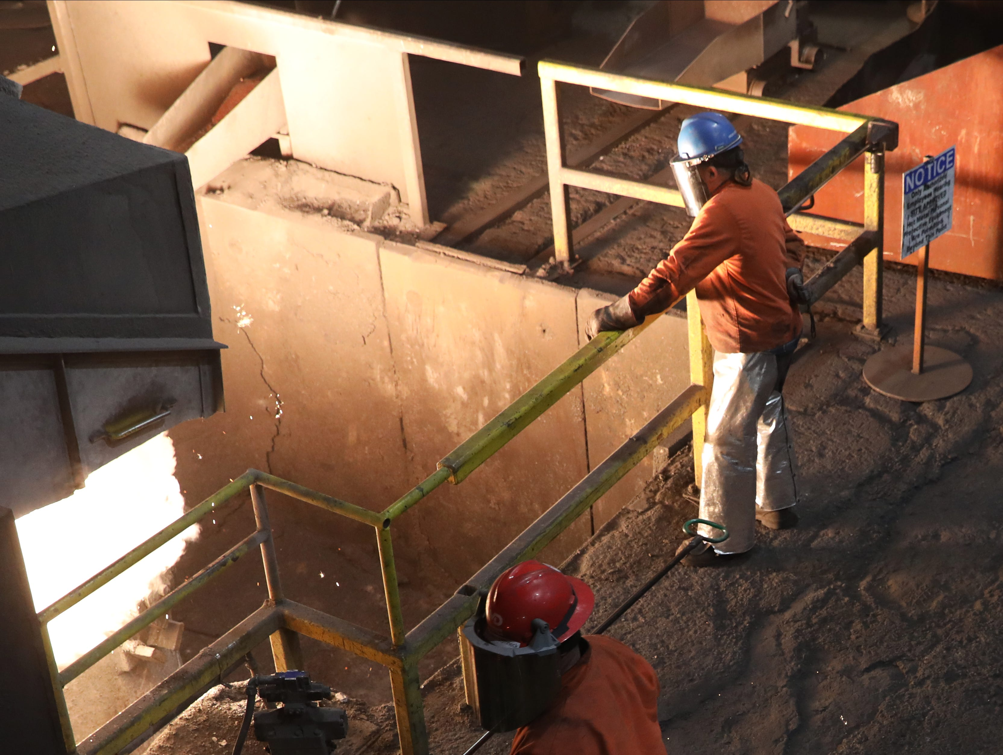 A worker takes a sample of molten iron from a crucible being filled to make pipe at McWane Ductile in Coshocton.