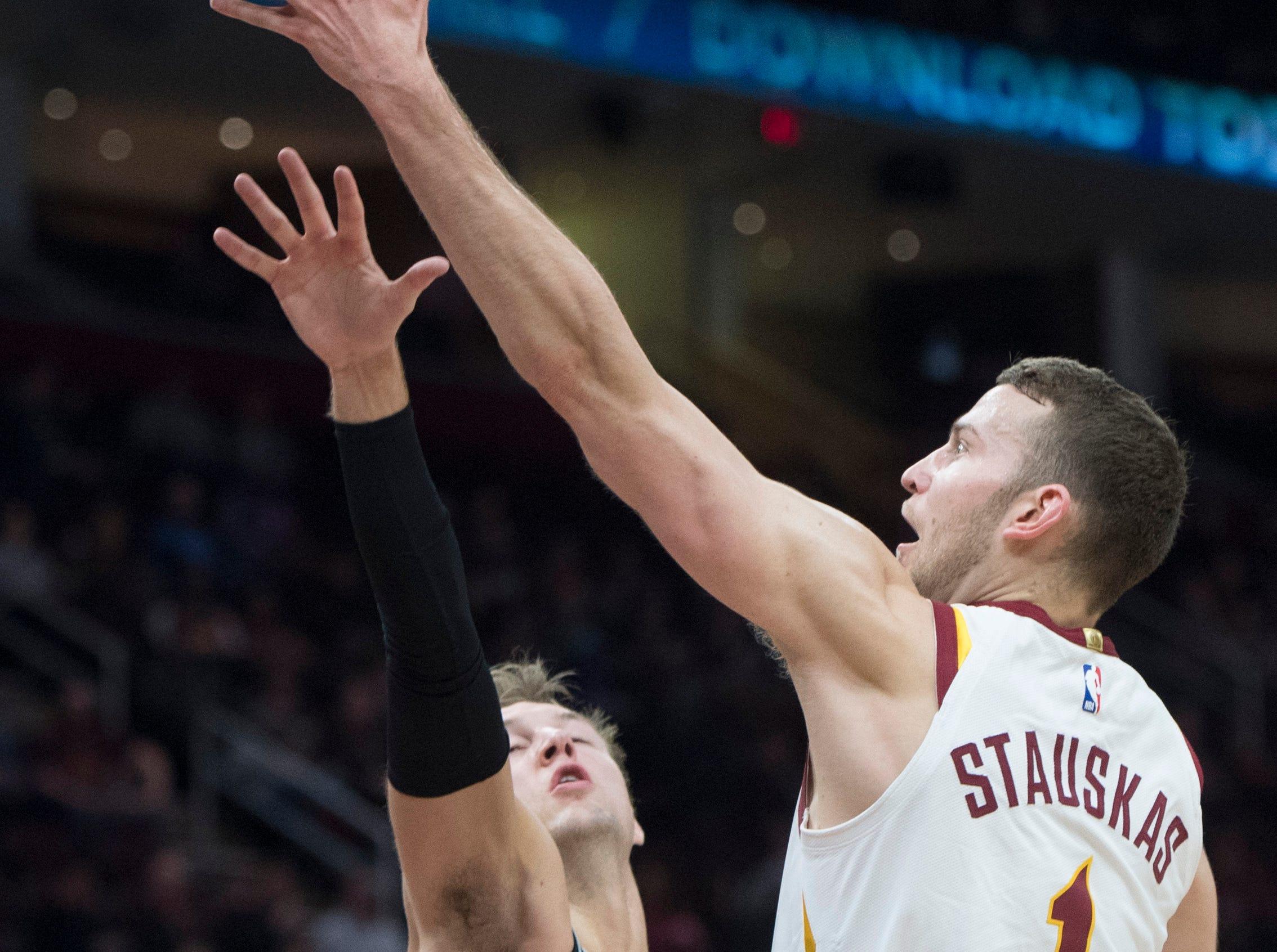 Cleveland Cavaliers guard Nik Stauskas shoots over Detroit Pistons guard Luke Kennard in the first half of an NBA basketball game.