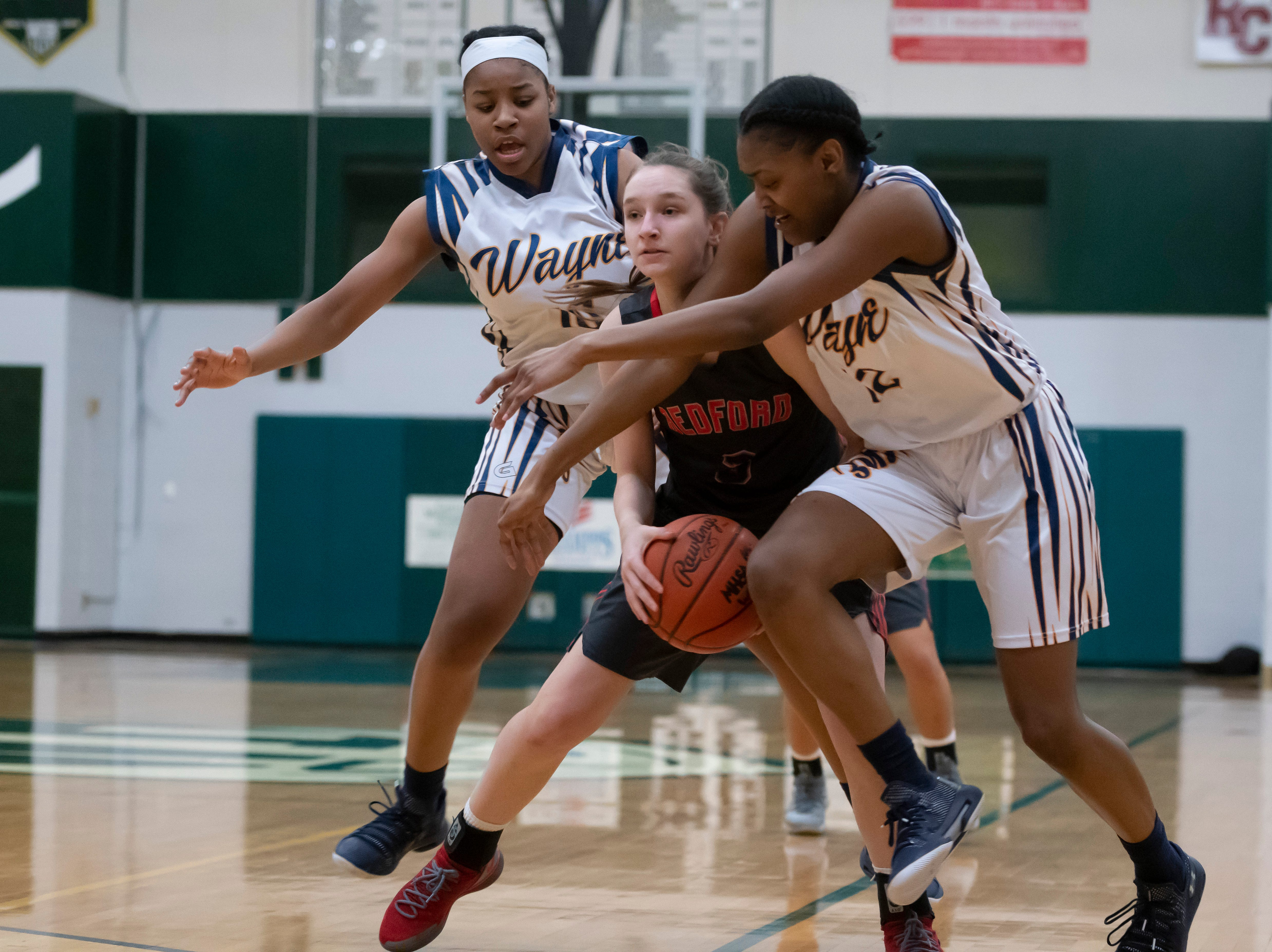 Wayne Memorial guard Jeanae Terry, left, and forward Jayah Hicks try to steal the ball from Bedford's Madison Norton during the first half.