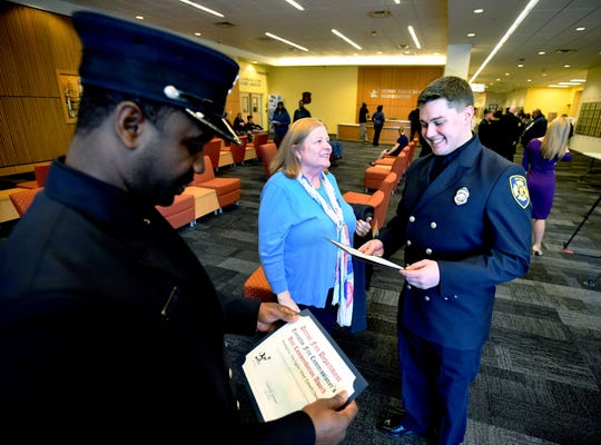 Firefighter Kenneth Durant and Thomas Haberstick look over the certificates they received for their life-saving actions in a March fire, with Haberstick's mother, Jennifer Haberstick, proudly looking on.