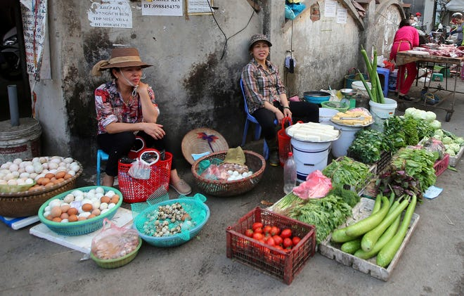 A woman sells vegetables at an outdoor market in Hanoi, Vietnam, Thursday, Feb. 21, 2019. Vietnam, the location of President Donald Trump's next meeting with North Korean leader Kim Jong Un, has come along way since the Us abandoned its war against communist North Vietnam in the 1970s. (AP Photo/Minh Hoang)