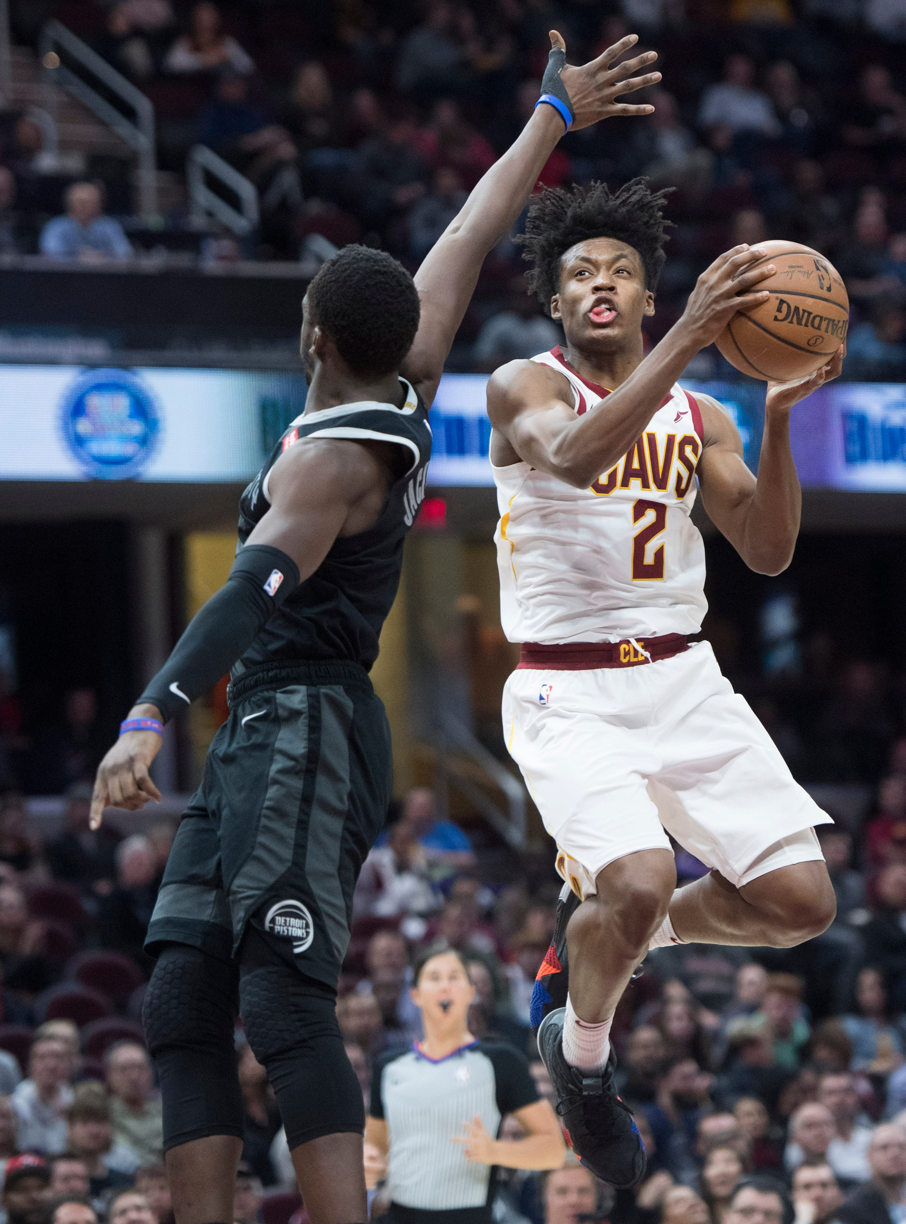Cleveland Cavaliers' guard Collin Sexton drives to the basket against Detroit Pistons' guard Reggie Jackson, from Italy, in the first half of an NBA basketball game, Monday, March 18, 2019, in Cleveland.