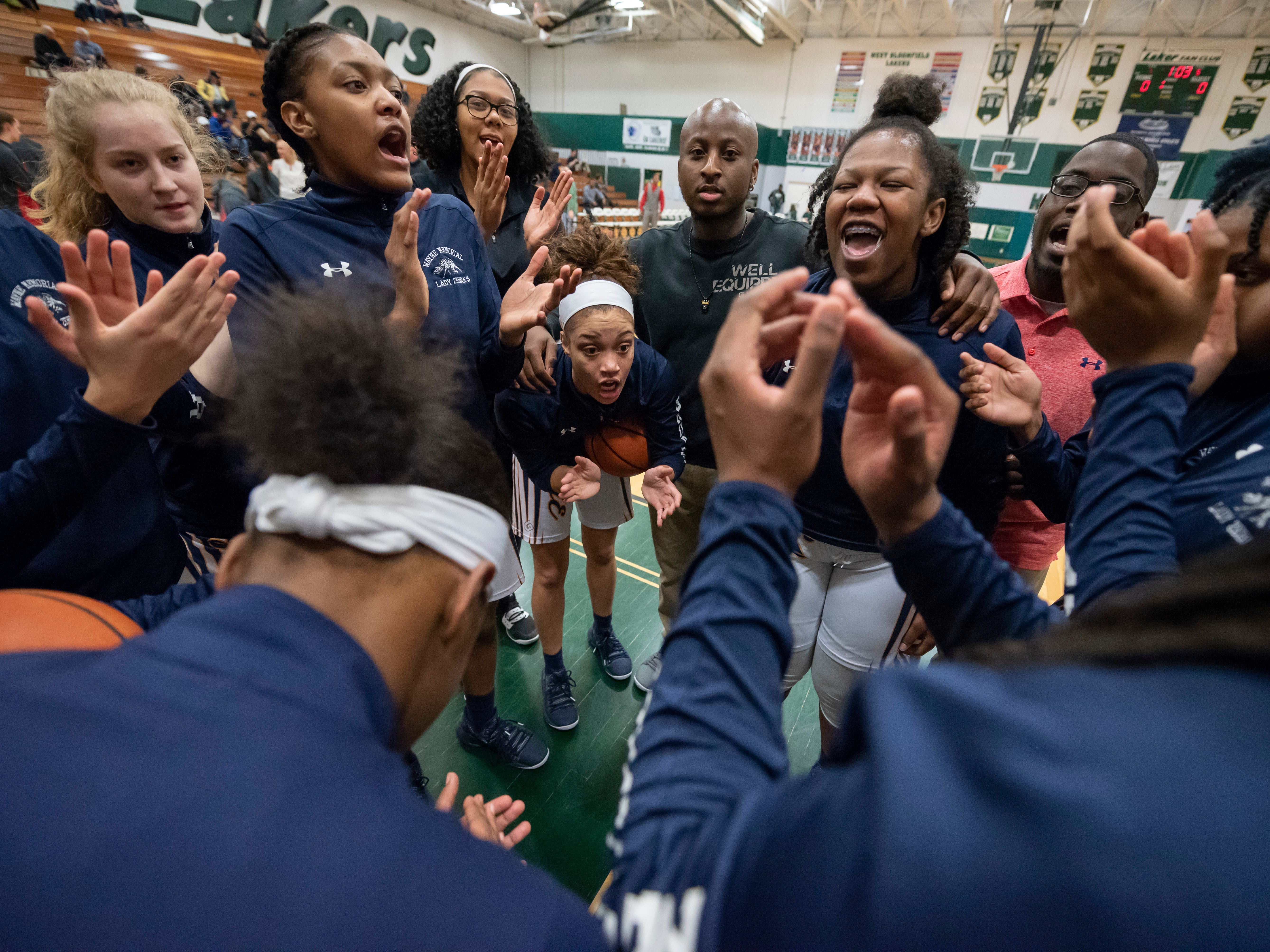 The Wayne Memorial girls basketball team rallies together before the start of a quarterfinals high school basketball playoffs game against Temperance Bedford at West Bloomfield High School, March 19, 2019. Wayne Memorial defeated Temperance Bedford 50-28.