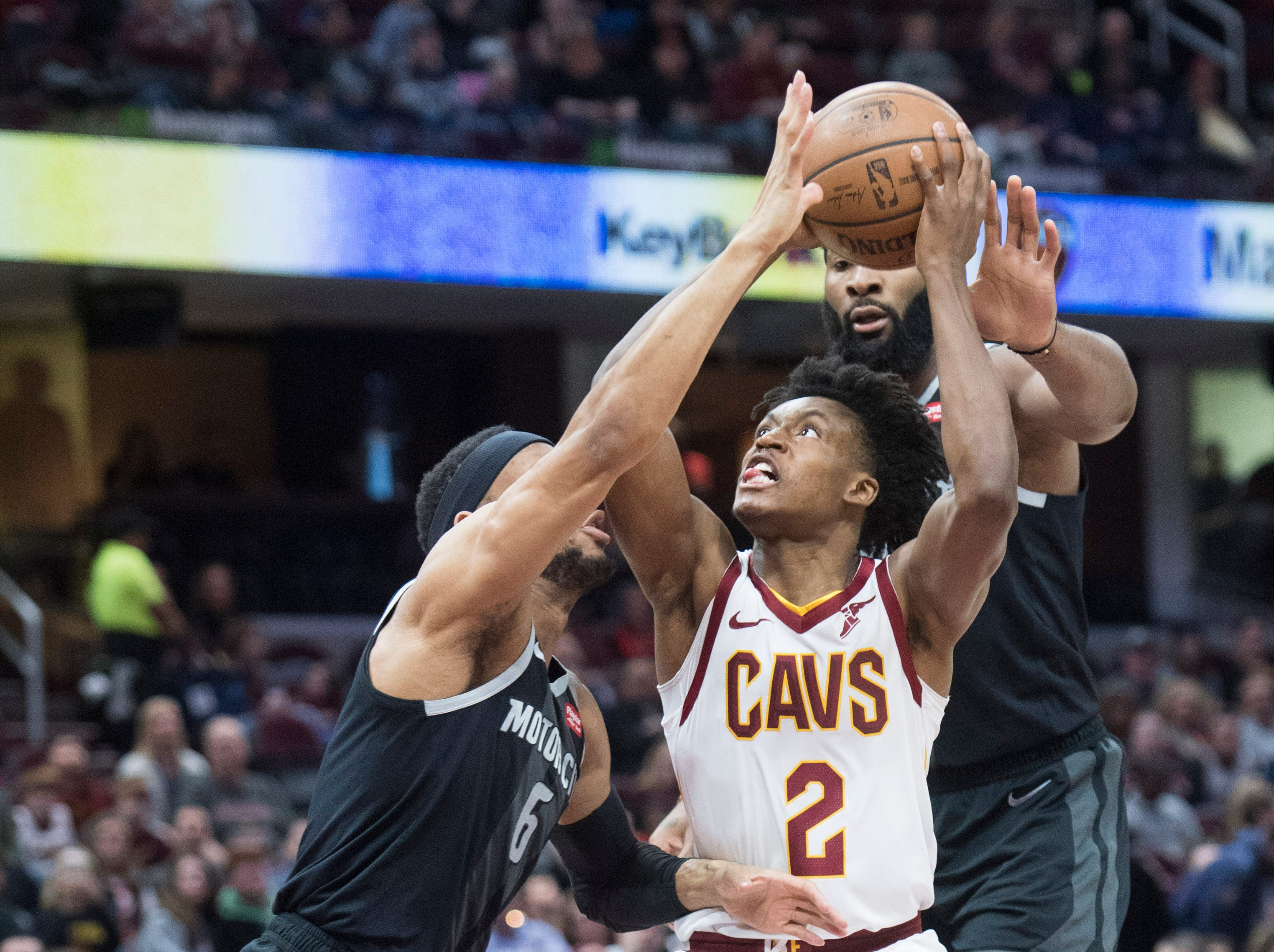 Cleveland Cavaliers' guard Collin Sexton drives to the basket between Detroit Pistons' guard Bruce Brown and center Andre Drummond in the first half of an NBA basketball game.