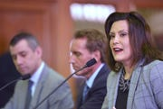 (L-R): Deputy State Budget Director Kyle Jen and Budget Director Chris Kolb join MI Gov. Gretchen Whitmer as she presents her 'fiscal year 20 budget proposal,' called, 'The Road To Opportunity,' to lawmakers during a joint meeting of the House and Senate appropriations committees in the Senate Hearing Room on the ground floor of the Boji Tower in Lansing, Tuesday morning, March 5, 2019.