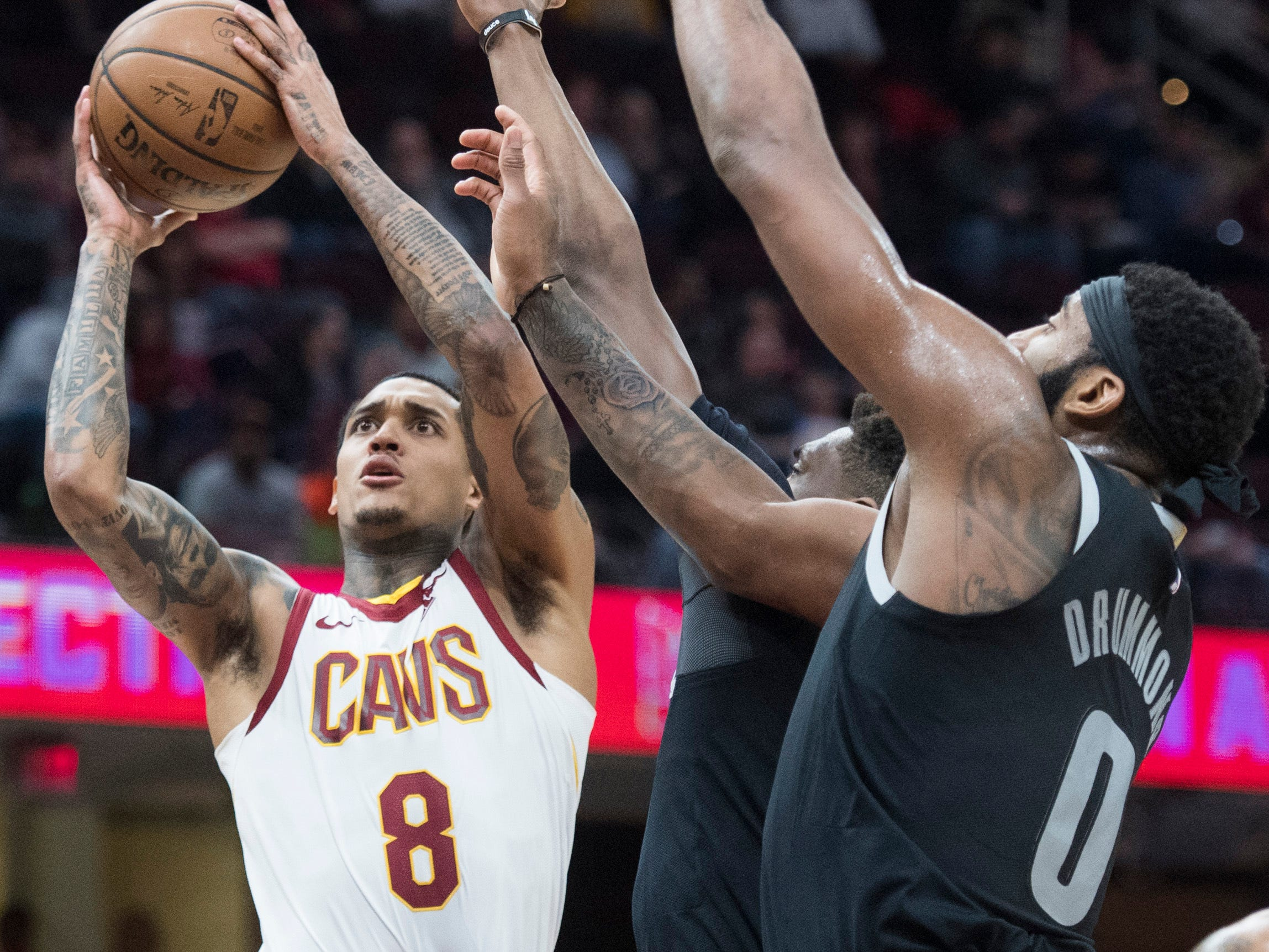 Cleveland Cavaliers' guard Jordan Clarkson, left, drives to the basket against Detroit Pistons' guard Langston Galloway and center Andre Drummond in the first half of an NBA basketball game.