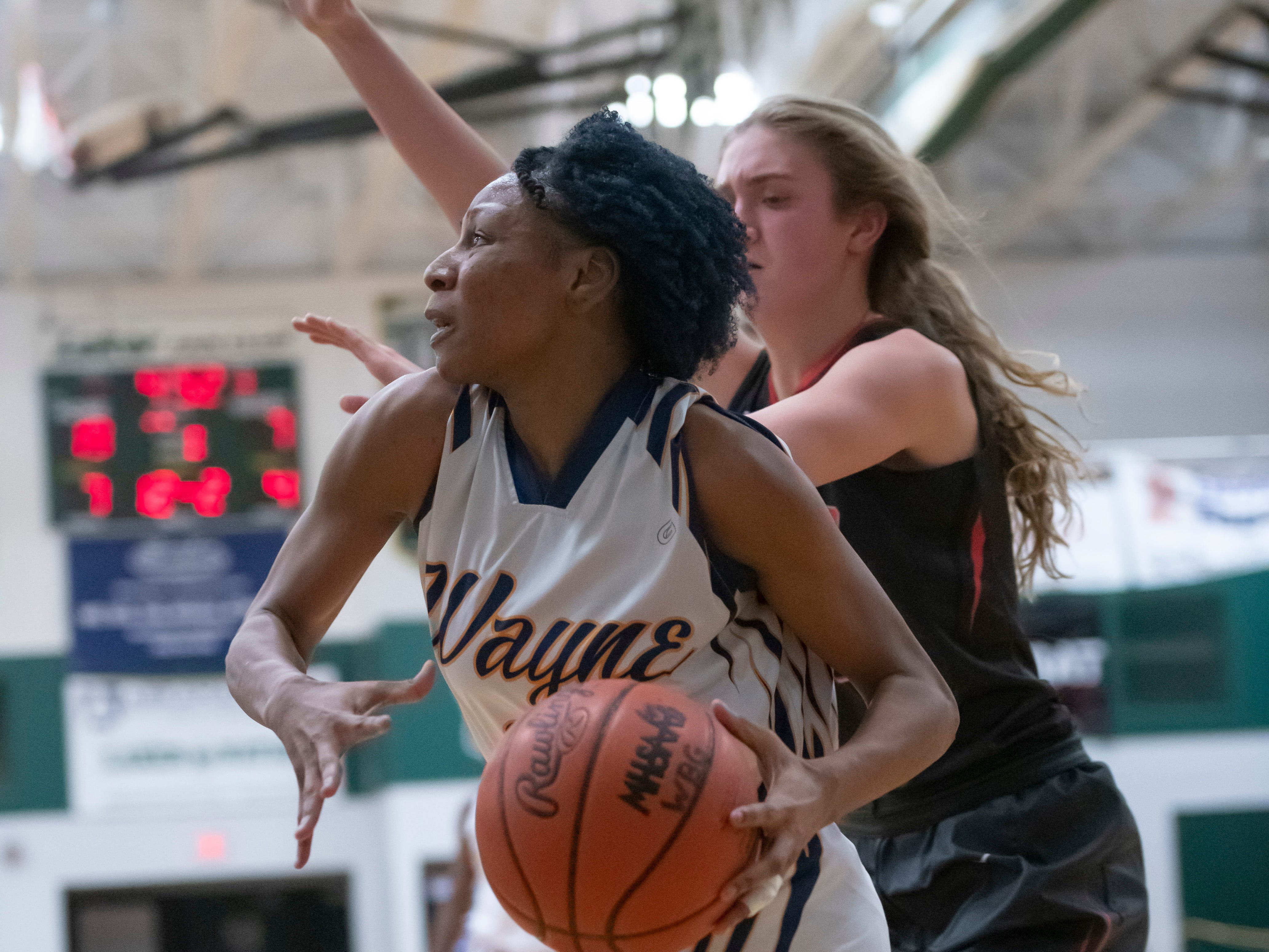 Wayne Memorial guard Sammiyah Hoskin drives the ball to the basket while under pressure from Bedford's Sophia Gray in the first half.