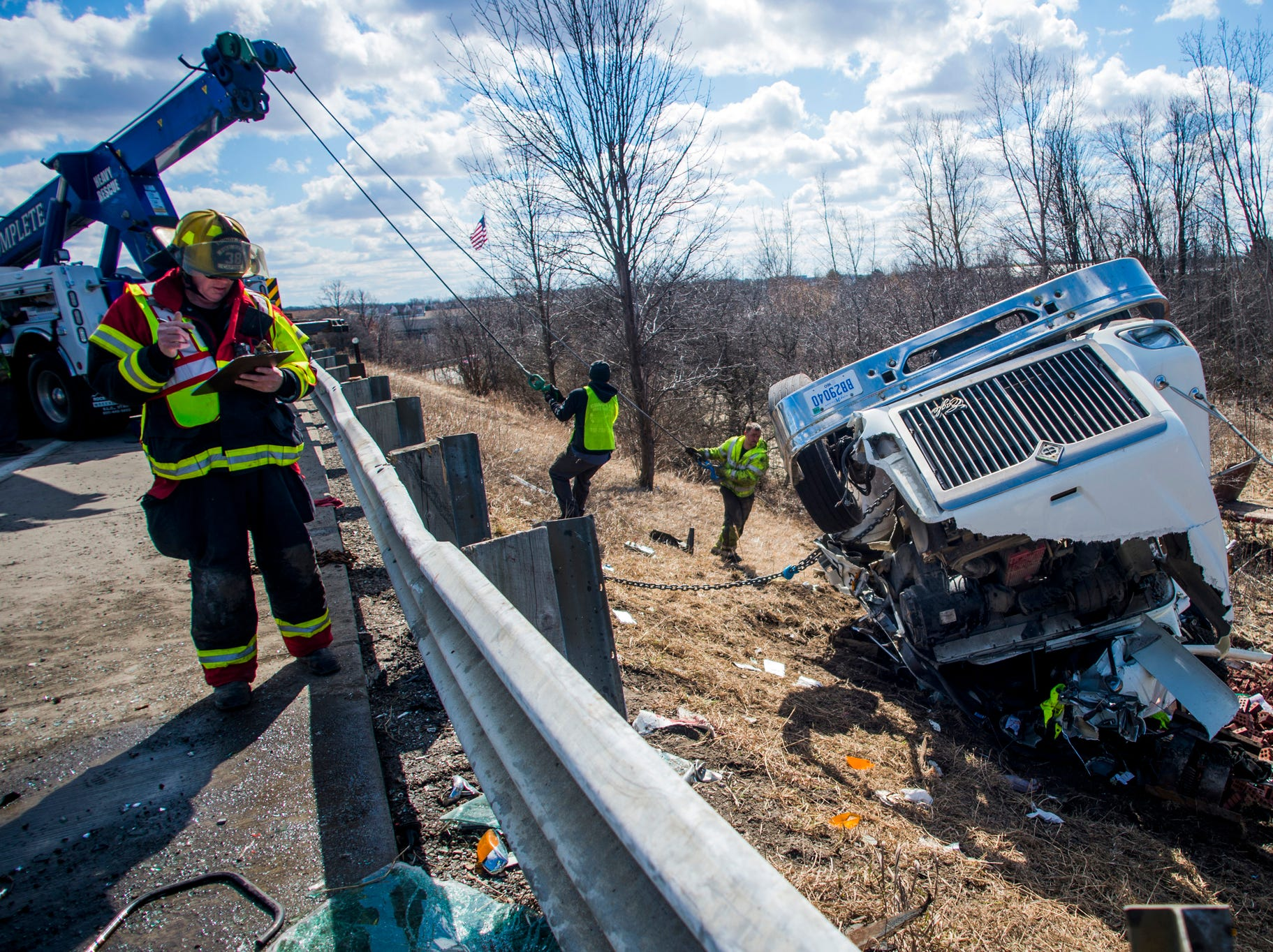 Mundy Township Fire Captain John Sheridan takes notes as workers hook the cab of an overturned semitrailer to a tow truck on southbound Interstate 75 after the U.S. 23 split on Monday, March 18, 2019. The driver was transported to a local hospital.
